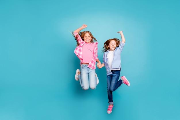 Una foto a figura intera di due ragazze libere incoraggiate esultanti che saltano mentre sono isolate con sfondo blu