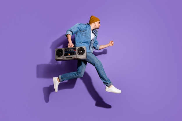 Foto di dimensioni del corpo a figura intera del ragazzo bello urgente in camicia di jeans jeans che tiene il registratore audio retrò con la mano che salta verso la discoteca isolato su sfondo di colore vivido viola viola
