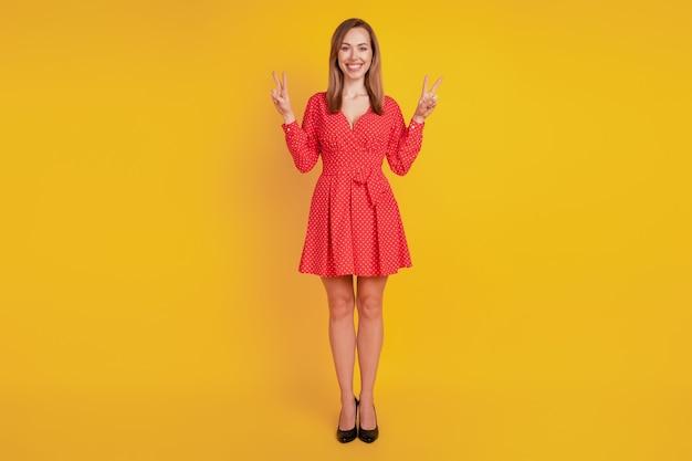 Le dimensioni del corpo a figura intera di una ragazza amichevole positiva mostrano due segni a v sul muro giallo