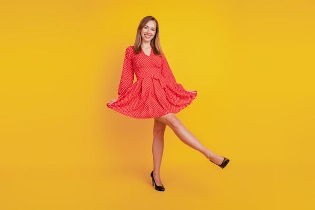 La dimensione del corpo a tutta lunghezza di una ragazza felice e positiva tiene la gonna rossa sul muro giallo