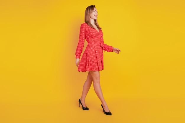 Foto del profilo a figura intera di una ragazza sicura di sé che cammina su sfondo giallo con un vestito corto rosso fantasia