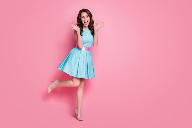 Vista laterale del profilo delle dimensioni del corpo a tutta lunghezza della ragazza che si diverte in posa di sfondo di colore rosa isolato
