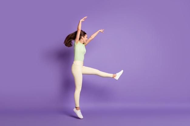 Vista laterale del profilo delle dimensioni del corpo integrale di bella ragazza allegra allegra allegra funky sportiva che salta danza professionale mossa isolato luminoso vivido splendore vibrante lilla viola colore sfondo