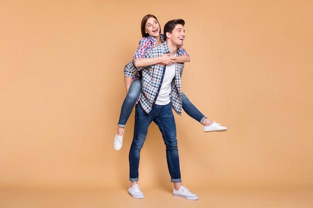 Le dimensioni del corpo a figura intera hanno girato la foto di una coppia bianca carina carina positiva allegra che indossa jeans denim con lei che gli ha cavalcato la schiena e lui che la portava isolata su sfondo beige