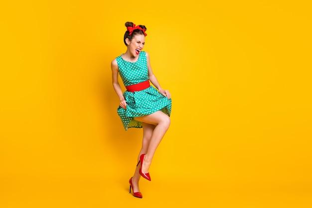 Vista a figura intera delle dimensioni del corpo di una ragazza allegra attraente che balla divertendosi godendosi il divertimento isolato su uno sfondo di colore giallo brillante