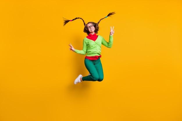 Vista a tutta lunghezza delle dimensioni del corpo di una ragazza allegra e funky attraente che salta mostrando il segno v che si diverte con uno sfondo di colore giallo brillante isolato