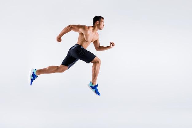Vista a figura intera delle dimensioni del corpo di un attraente ragazzo sportivo professionista che salta in esecuzione