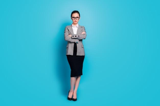 Vista a tutta lunghezza delle dimensioni del corpo di un datore di lavoro di donna seria intelligente e intelligente con le braccia piegate isolate su uno sfondo di colore blu brillante