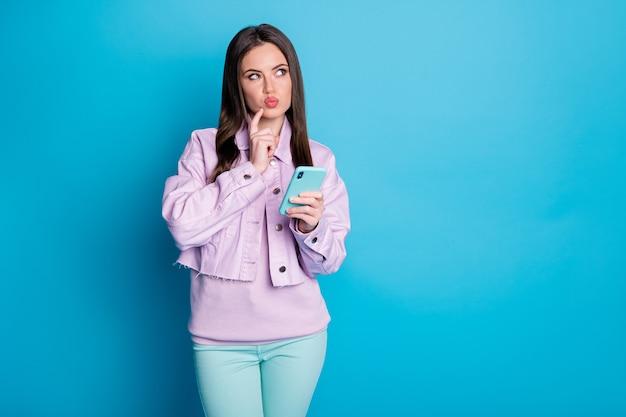 Vista a tutta lunghezza delle dimensioni del corpo di una ragazza allegra che utilizza un dispositivo isolato su sfondo blu