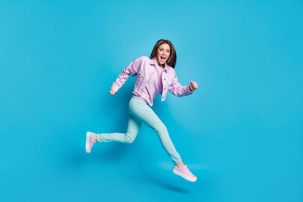 Vista a figura intera delle dimensioni del corpo di una ragazza allegra che si diverte a saltare isolata su uno sfondo di colore blu