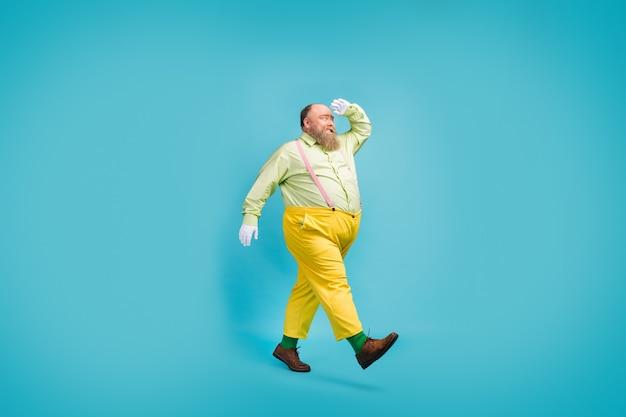 Vista integrale delle dimensioni del corpo dell'uomo allegro che cammina guardando lontano