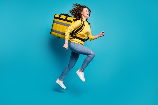 Vista a tutta lunghezza delle dimensioni del corpo della ragazza che salta portando il pacchetto divertendosi sfondo blu isolato