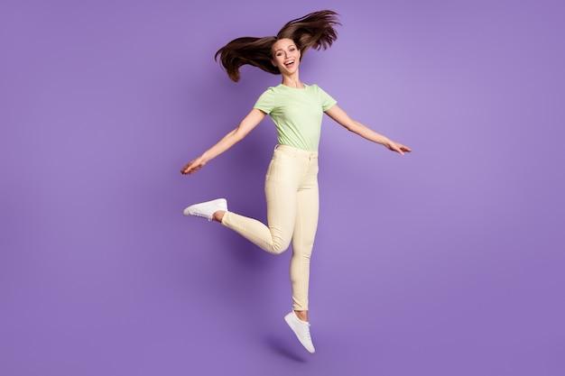 Vista a tutta lunghezza delle dimensioni del corpo di lei bella attraente bella spensierata allegra allegra funky ragazza che salta ballando divertendosi isolato luminoso vivido splendore vibrante lilla viola colore sfondo