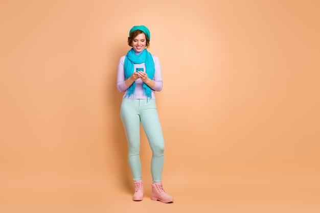 Vista a figura intera delle dimensioni del corpo di lei, bella attraente bella bella allegra ragazza allegra che utilizza un dispositivo digitale che trascorre il tempo libero libero isolato su sfondo beige color pastello