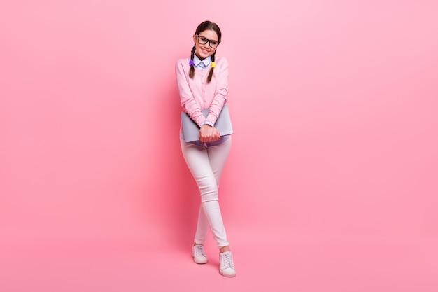 Vista a tutta lunghezza del corpo di lei, lei, bella, attraente, carina, allegra, modesta, dai capelli castani, adolescente, che tiene in mano il computer portatile in posa isolato su sfondo rosa color pastello