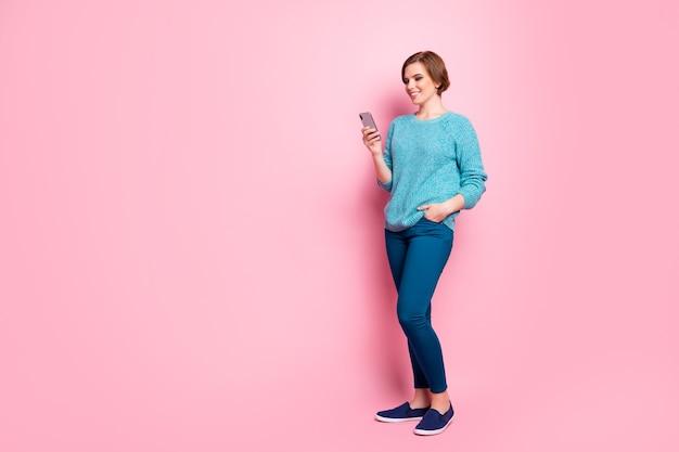 Vista a figura intera di lei è bella ragazza dai capelli castani allegra abbastanza adorabile attraente che utilizza il cellulare in chat con il servizio web di fidanzato