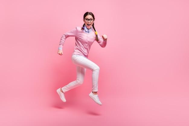 Vista a tutta lunghezza delle dimensioni del corpo di lei bella attraente bella adorabile allegra allegra funky sportiva ragazza adolescente nerd che salta in esecuzione lezione 1 settembre isolato sfondo rosa color pastello