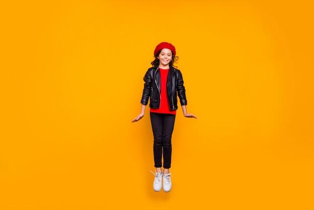 Vista di tutta la lunghezza del corpo di lei bella attraente alla moda allegra allegra funky timida ragazza dai capelli lunghi che salta per divertirsi isolato sopra la parete di colore giallo vibrante brillante brillante brillantezza