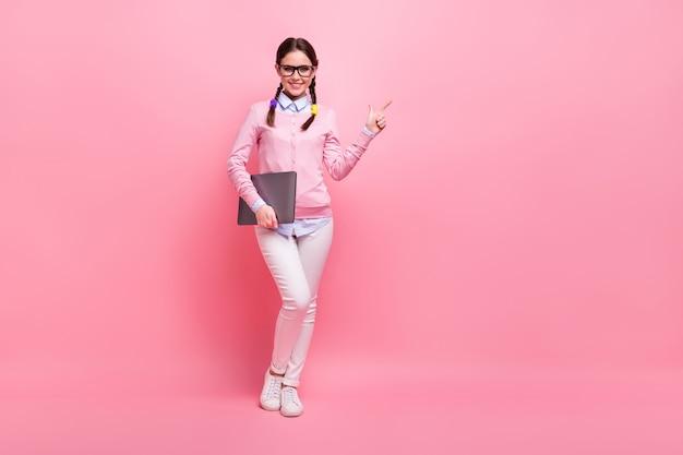 Vista a tutta lunghezza delle dimensioni del corpo di lei, bella ragazza adolescente dai capelli castani allegra e sicura che tiene in mano il computer portatile che dimostra copia spazio annuncio imparare studio isolato rosa pastello colore sfondo