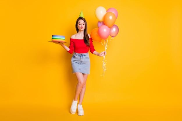 Vista a tutta lunghezza delle dimensioni del corpo di lei, bella ragazza attraente civettuola che tiene in mano una torta domestica fresca, palle d'aria, invio di un bacio, isolato, brillante, vivido, brillante, vibrante, colore giallo, fondo