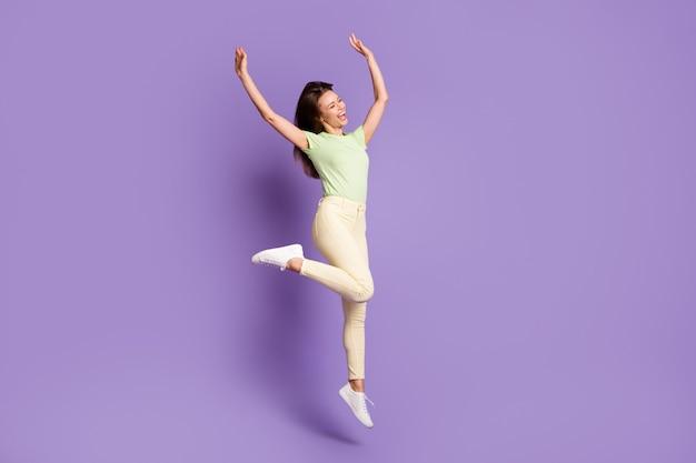 Vista a tutta lunghezza delle dimensioni del corpo di lei, lei, attraente, bella, snella, allegra, allegra, ragazza che salta, balla, gode, riposo, festa, isolato, luminoso, vivido, splendore, vibrante, lilla, viola, colore, fondo