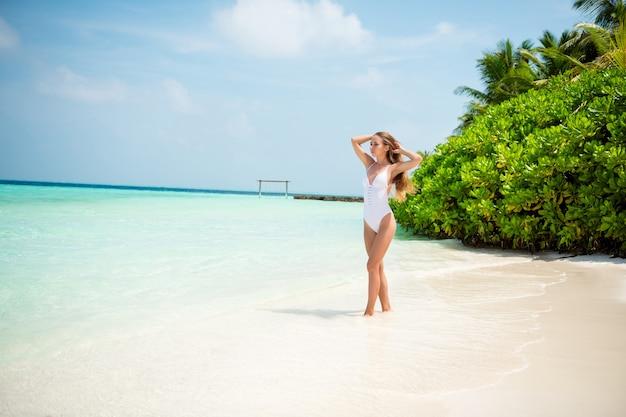 Vista a tutta lunghezza delle dimensioni del corpo di lei, bella ragazza sportiva e sottile, snella, che cammina godendosi una giornata calda e soleggiata, destinazione resort internazionale, isola pulita e pura sabbia plage