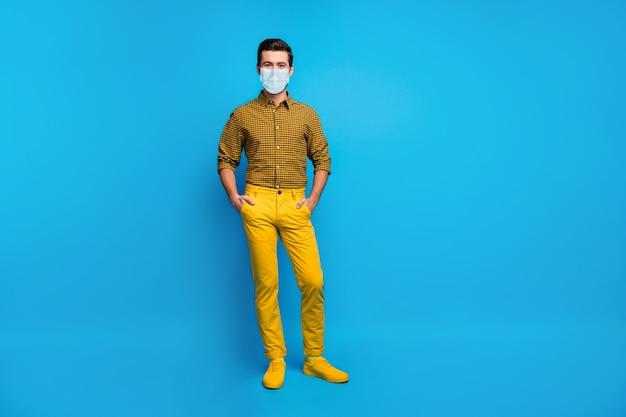 Vista a figura intera delle dimensioni del corpo del suo ragazzo contento che indossa una maschera di garza ferma la polmonite virale cina wuhan mers cov contaminazione aria co2 inquinamento isolato su sfondo di colore vibrante