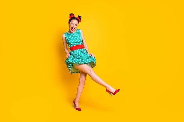 Vista a tutta lunghezza del corpo di una bella ragazza allegra che balla divertendosi godendosi l'evento isolato su uno sfondo di colore giallo brillante