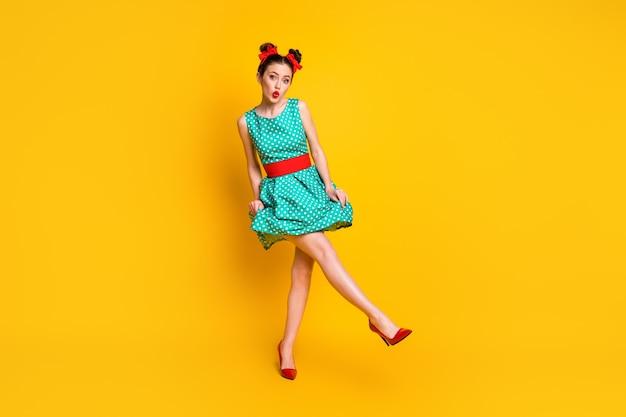 Vista a tutta lunghezza delle dimensioni del corpo di una bella ragazza funky carina che balla divertendosi con le labbra imbronciate isolate su uno sfondo di colore giallo brillante