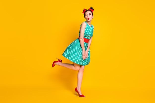 Vista a tutta lunghezza delle dimensioni del corpo di una bella ragazza timida timida che balla in posa labbra imbronciate isolate su uno sfondo di colore giallo brillante