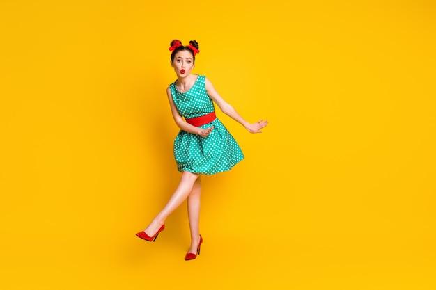 Vista a tutta lunghezza del corpo di una bella ragazza funky che balla divertendosi a mandare un bacio d'aria isolato su uno sfondo di colore giallo brillante