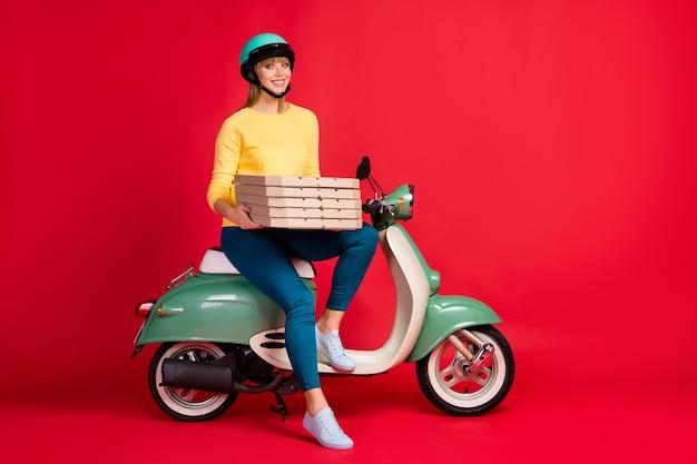 Vista integrale delle dimensioni del corpo di una bella ragazza seduta sul ciclomotore che trasportano scatole per pizza