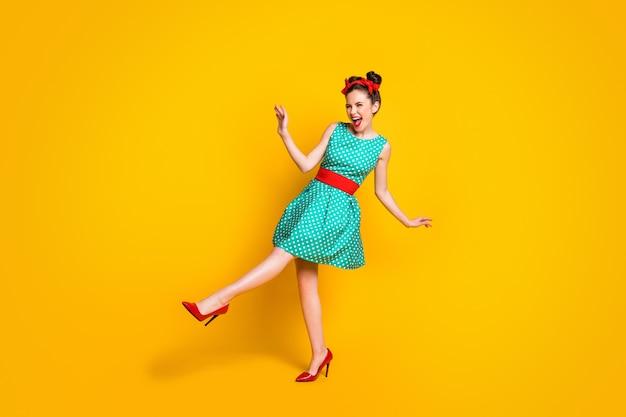 Vista a tutta lunghezza delle dimensioni del corpo di una bella ragazza allegra contenta che balla divertendosi godendosi la discoteca isolata su uno sfondo di colore giallo brillante