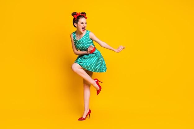 Vista a tutta lunghezza del corpo di una bella ragazza allegra e snella che balla in discoteca divertendosi a rilassarsi isolata su uno sfondo di colore giallo brillante
