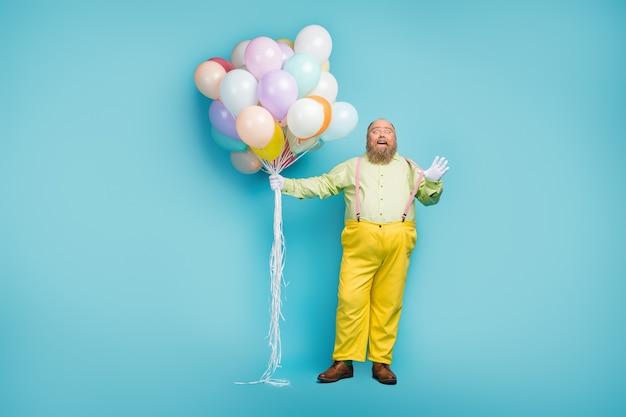 Vista a figura intera di un ragazzo maturo che trasporta palloni d'aria