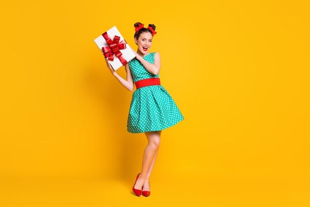 Vista a tutta lunghezza del corpo di una bella ragazza allegra attraente che tiene in mano una scatola regalo romantica isolata su uno sfondo di colore giallo brillante