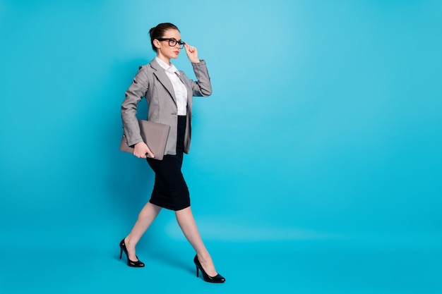 Vista a tutta lunghezza delle dimensioni del corpo di una bella ragazza attraente e di classe leader che trasporta un laptop che va isolato su uno sfondo di colore blu brillante