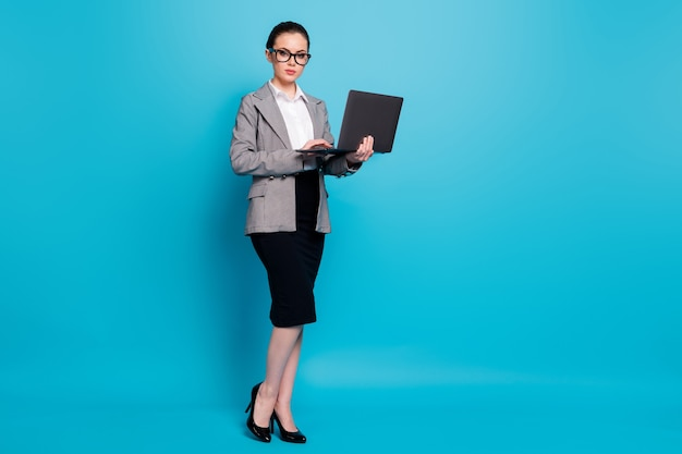 Vista a tutta lunghezza delle dimensioni del corpo di una bella specialista di classe che tiene in mano un laptop isolato su uno sfondo di colore blu brillante