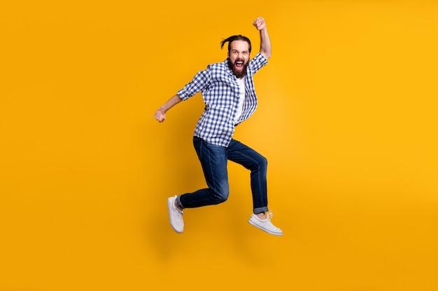Vista di tutta la lunghezza del corpo del ragazzo barbuto allegro felicissimo pazzo funky simpatico in camicia a quadri che salta su