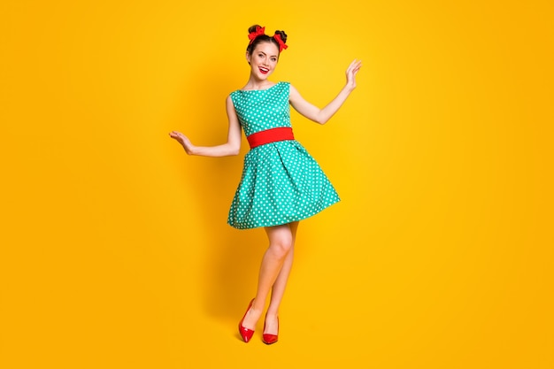 Vista a tutta lunghezza delle dimensioni del corpo di una ragazza allegra dall'aspetto gradevole che indossa un abito verde acqua in posa divertendosi isolata su uno sfondo di colore giallo brillante