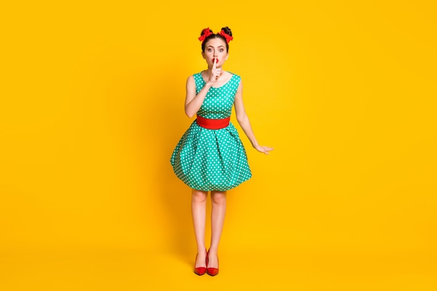 Vista a tutta lunghezza delle dimensioni del corpo di una bella ragazza carina che indossa un abito punteggiato verde acqua che mostra il segno shh isolato su uno sfondo di colore giallo brillante