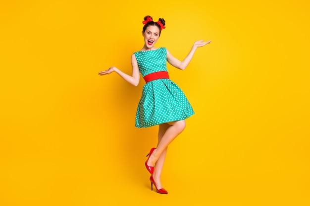 Vista a tutta lunghezza delle dimensioni del corpo di una bella ragazza allegra abbastanza contenta che indossa un vestito verde acqua che balla divertendosi isolata su uno sfondo di colore giallo brillante