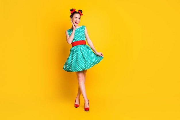 Vista a tutta lunghezza delle dimensioni del corpo di una bella ragazza allegra e magra che indossa un vestito verde acqua che si gode la camminata isolata su uno sfondo di colore giallo brillante