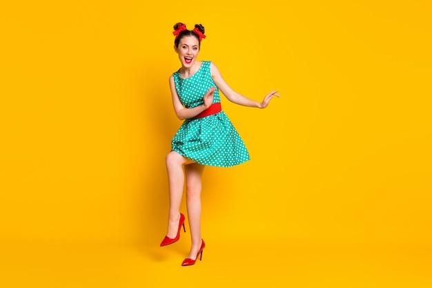 Vista a figura intera delle dimensioni del corpo di una ragazza abbastanza allegra che balla divertendosi riposando il tempo libero isolato su uno sfondo di colore giallo brillante