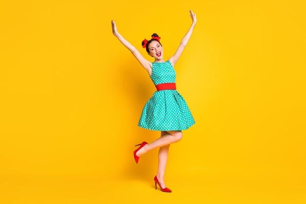 Vista a tutta lunghezza del corpo di una ragazza allegra piuttosto magra che si diverte alzando le mani in alto ballando isolata su uno sfondo di colore giallo brillante