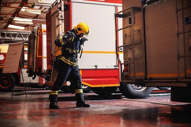 Tutta la lunghezza del coraggioso vigile del fuoco in piedi nella stazione dei vigili del fuoco in piena uniforme protettiva e si prepara all'azione.