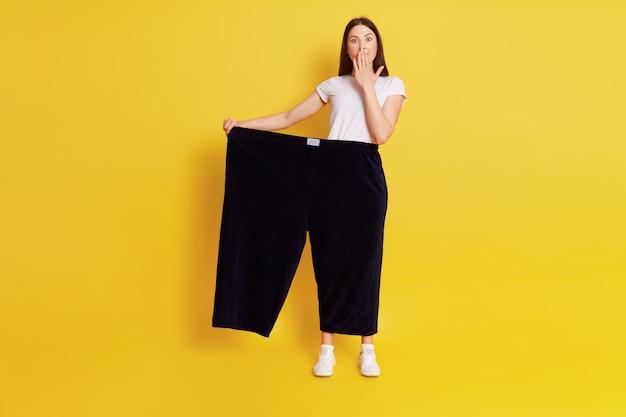 Tutta la lunghezza della femmina stupita caucasica ha perso peso e indossava vecchi pantaloni, essendo scioccata e coprendo la bocca con il palmo, in posa isolata sopra il muro giallo.
