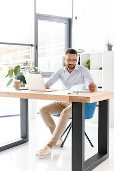Uomo d'affari non rasato caucasico integrale 30s in camicia bianca che lavora in ufficio sul computer portatile e che esamina appunti con documenti cartacei