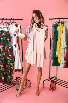 Tutta la lunghezza della donna affascinante in abito in piedi vicino al guardaroba con vestiti e scegliendo cosa indossare isolato sul rosa