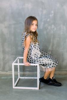 Integrale della bambina adorabile allegra in vestito grigio da modo che si siede sul cubo bianco